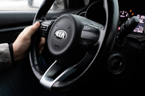 Kia-sedan-man-hand-on-steering-wheel