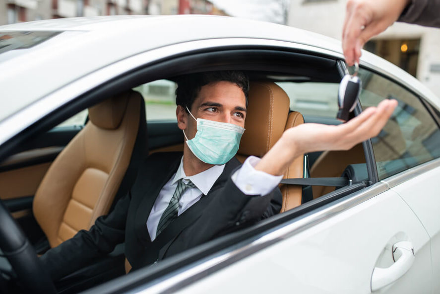 Masked-man-taking-the-car-keys-automotive-coronavirus-oncept