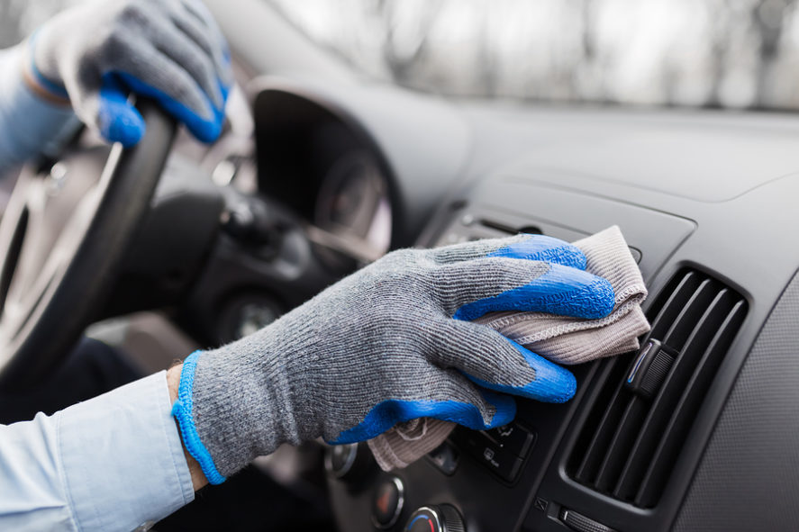 hands-wearing-gloves-cleaning-car-dash-interior