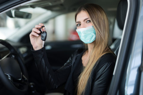 Masked-woman-showing-the-key-to-her-new-used-car
