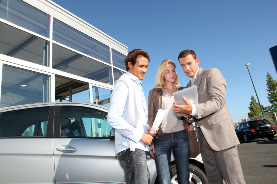 Car-Seller-With-Couple-Looking-At-Tablet-scaled