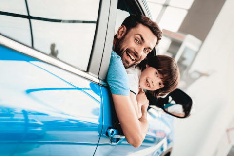 Man-&-child-in-blue-car-smiling